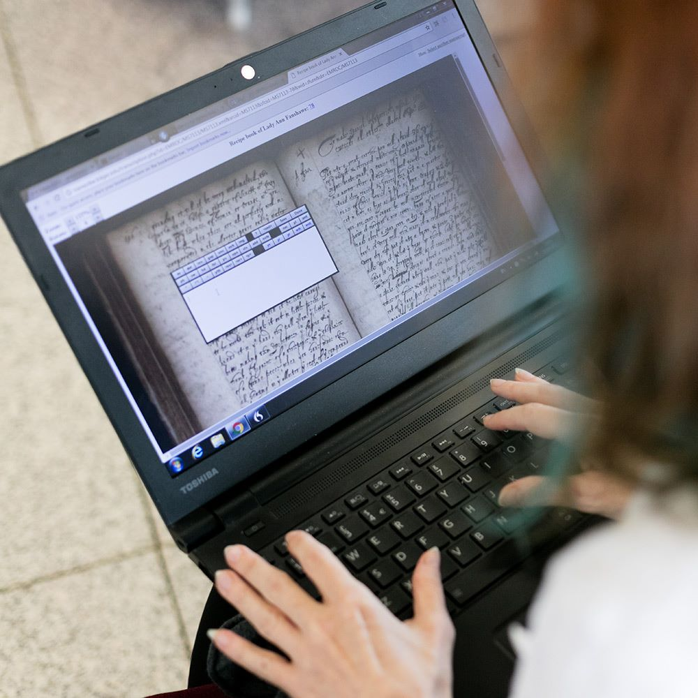 Student analyzing ancient text on a laptop
