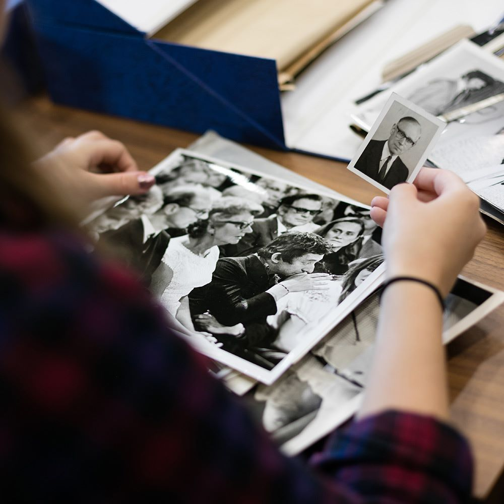 History student looking at black and white photos of people