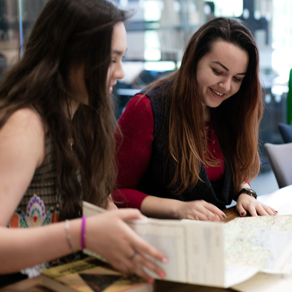 Two female history students looking through an old map resource