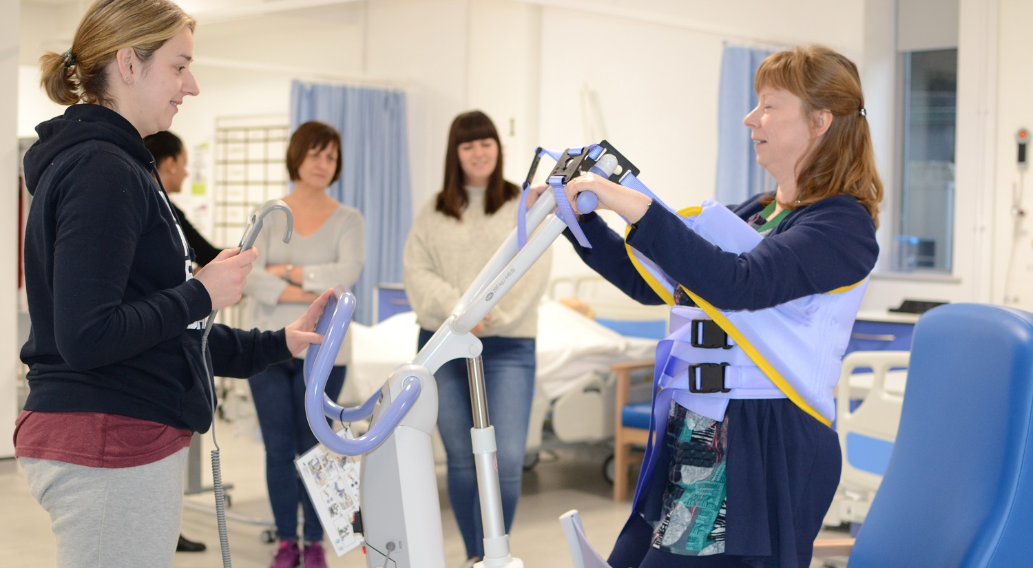 Erika Kerry from the School of Health and Social Care is standing on the left holding the control for an electronic hoist in her right hand. A mock-patient is on the right, with the hoist straps around her waist and under her arms. She is being lowered in to a blue chair. Two prospective students are standing in the background watching.