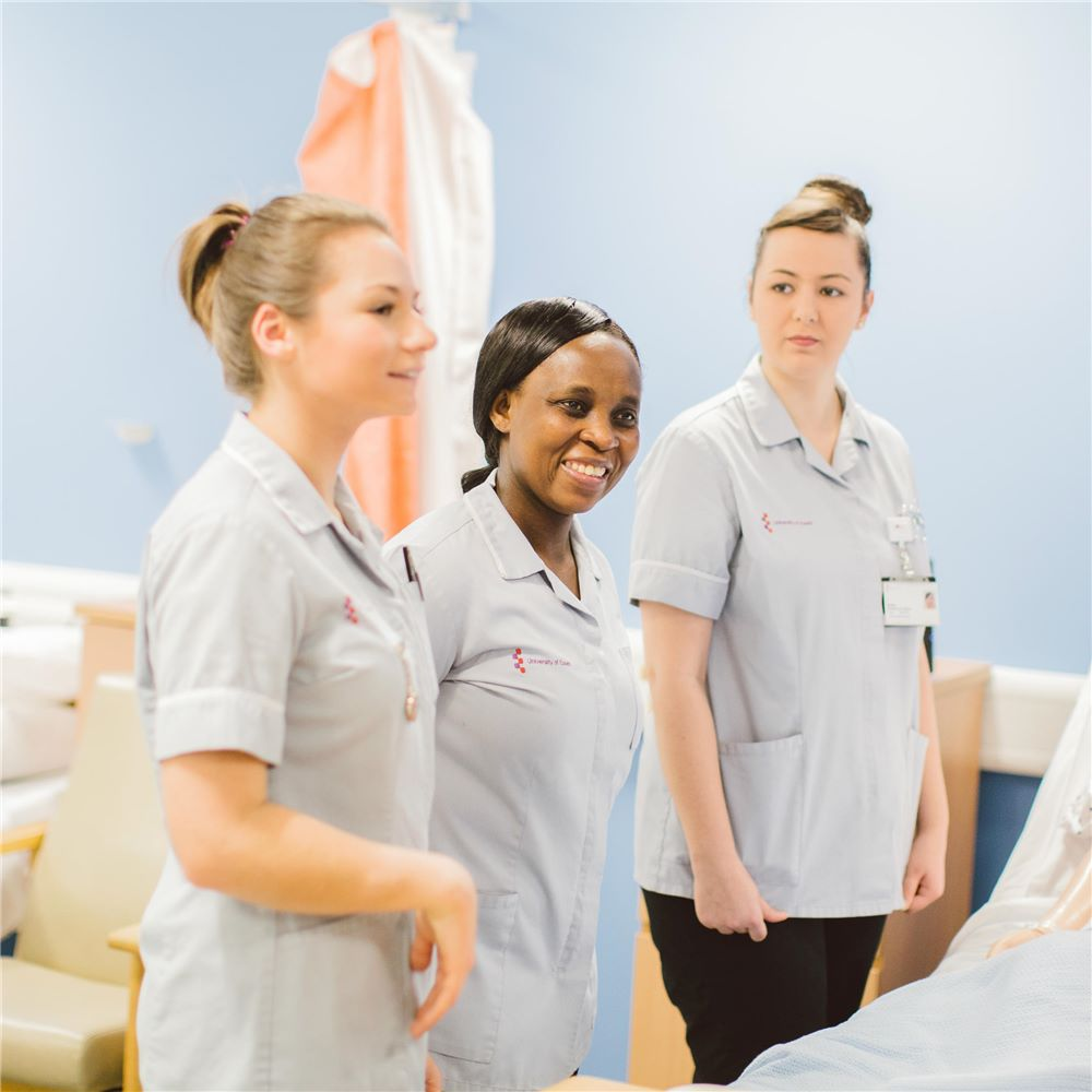 Three students in nurses uniforms standing next to a bed in a mock ward, listening to someone out of shot to the right of the photo.
