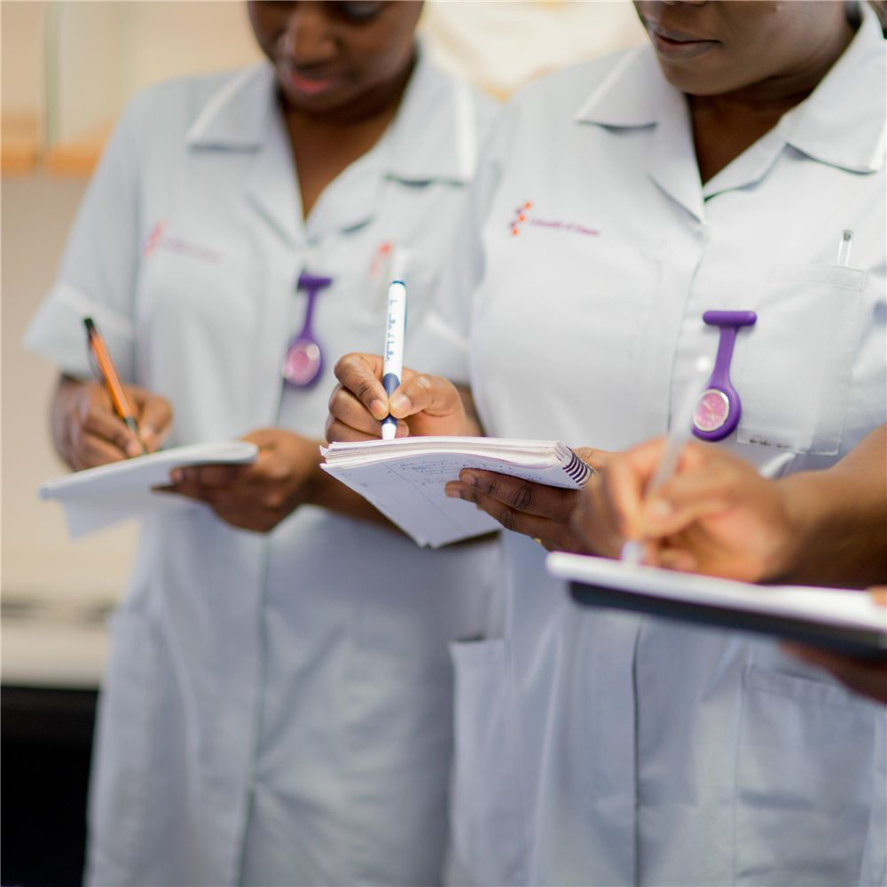 Two students in nursing uniforms, and a third mostly out of shot on the right, standing and writing notes on some paper in their hands.