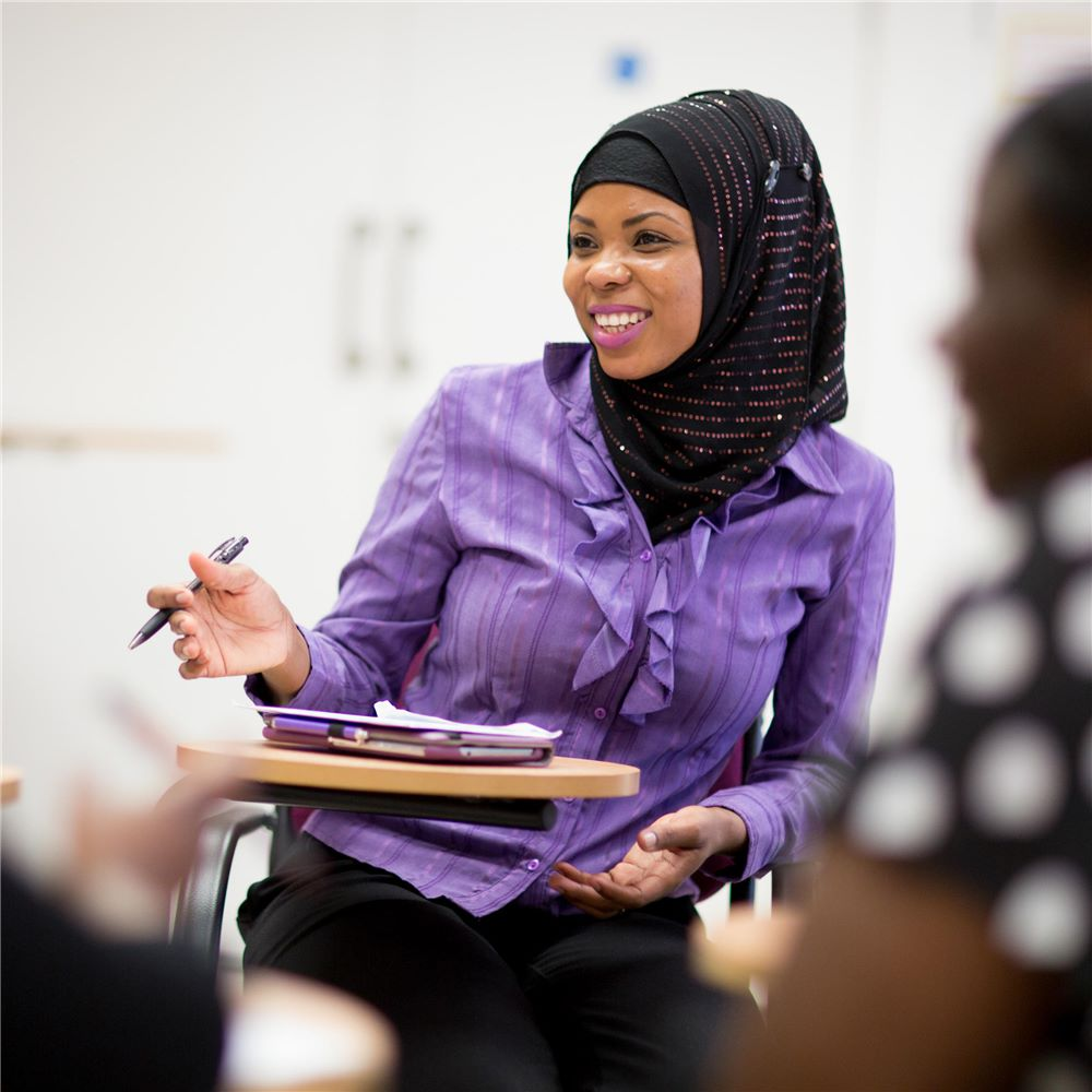 A student in a headscarf sitting in a seminar with a notebook in front of her, gesturing slightly with a pen in her right hand. A blurred second student is in the foreground to the right side of the photo.