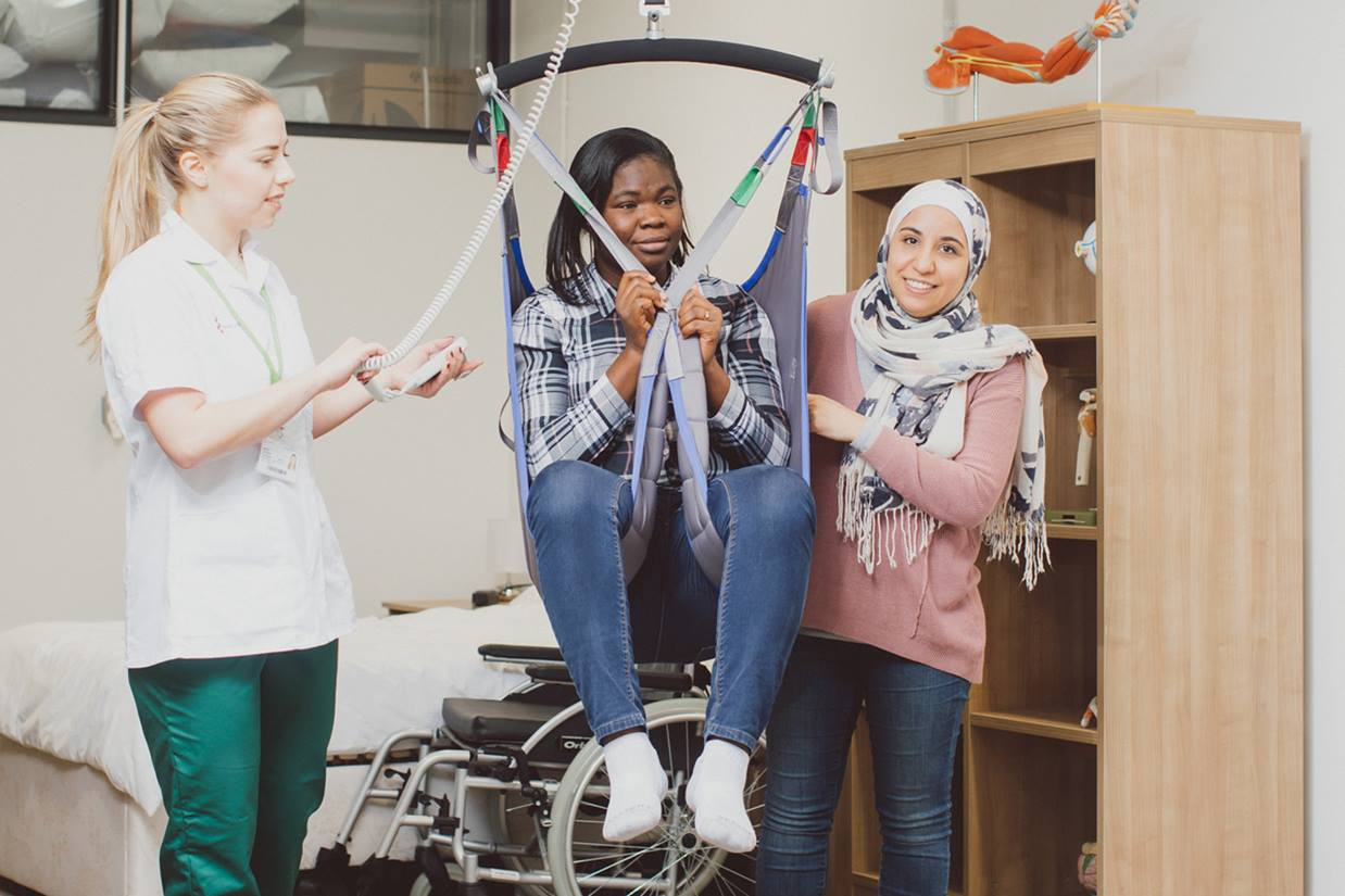 Two student Occupational Therapists moving a patient with a hoist