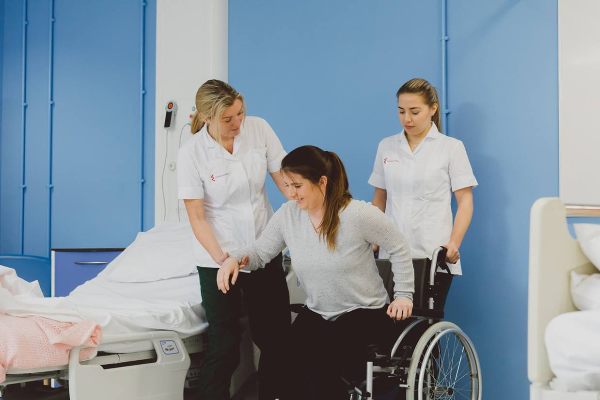 Two student Occupational Therapists helping a patient into a wheelchair