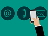 An illustration of a hand holding a phone in front of email and telephone logos