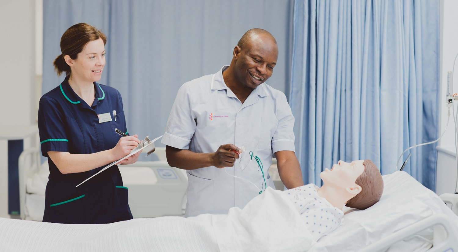 Kathy Burke is standing on the left holding a clipboard. To the right is a male nursing student holding an oxygen mask. In front of them is a Sim Man in a hospital bed in one of the School's mock wards.