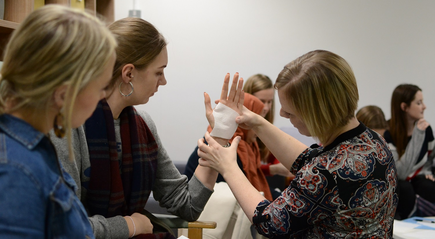 On the right, with her back to the camera, is Selena Hammond from the School of Health and Social Care. On the left are two students. The student in the middle has her elbow resting on the arm of her chair, her hand pointing up. Selena is holding a piece of sterile bandage against the hand, as part of a demonstration on how to make a splint. Several other students are sitting in the background.