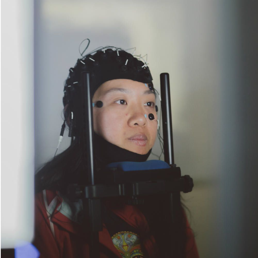 A student wearing a black EEG cap, resting her chin on a frame, with sensors attached to her face.