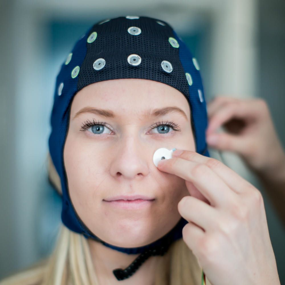 A woman with blonde hair wearing a blue EEG cap, with someone to the right attaching a small sensor to her cheek.
