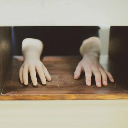 A pair of hands resting on the surface of a table.