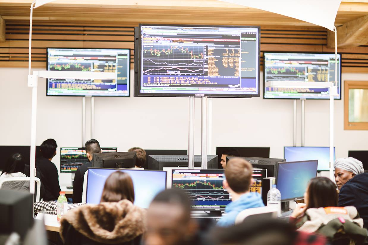 A wide shot of the Essex Business School Bloomberg trading floor with a busy class of students looking at the demonstration of financial data displayed on the large screens.