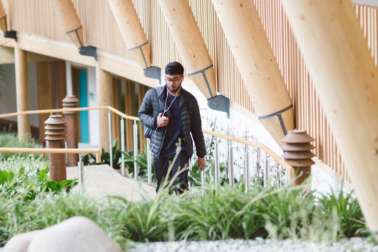 A sole male student walks through the winter garden of Essex Business School.