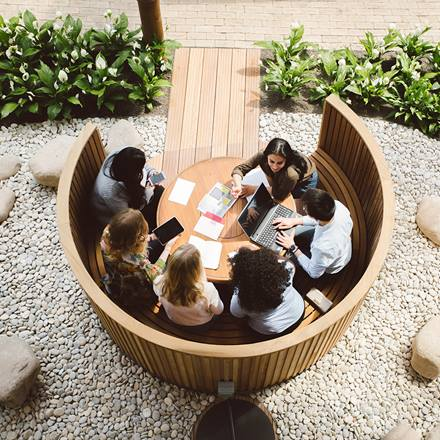 Essex Business School students sit and discuss work in one of the study pods in the Winter Garden which is situated in the Business School Building