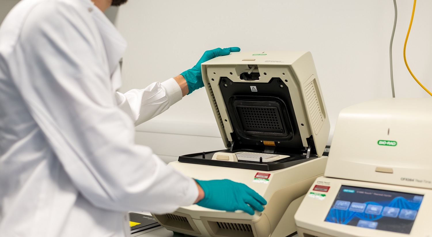 A person in a white lab coat and green gloves, lifting the lid on a piece of life sciences laboratory equipment.