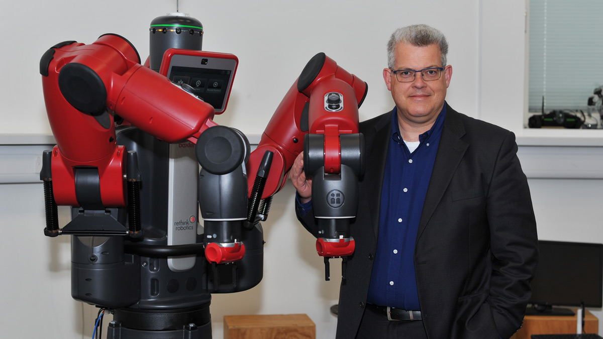 A photo of Professor Klaus McDonald-Maier, from the School of Computer Science and Electronic Engineering, standing next to a large red and black Baxter robot.)