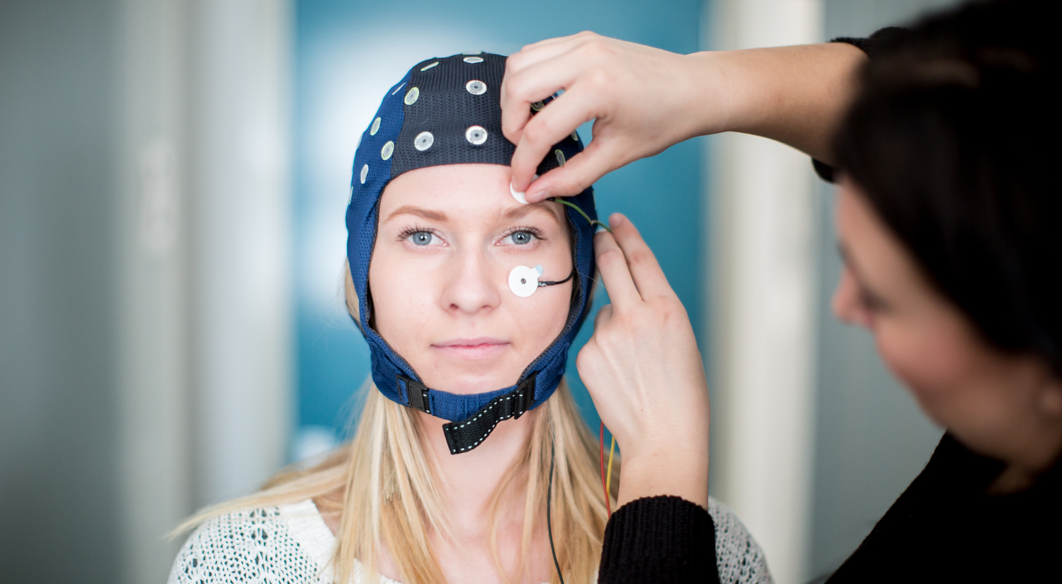 A woman wearing a blue EEG cap looking directly at the camera. A second person standing on the right of the shot is adjusting some sensors attached to her face, one above her left eyebrow and the other just underneath the same eye.