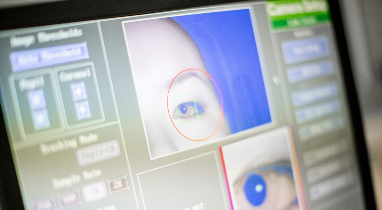 A photo of a computer screen which is showing results from an eye-tracking test. It includes a picture of the top right quarter of the subjects face, and a close-up shot of their eye.