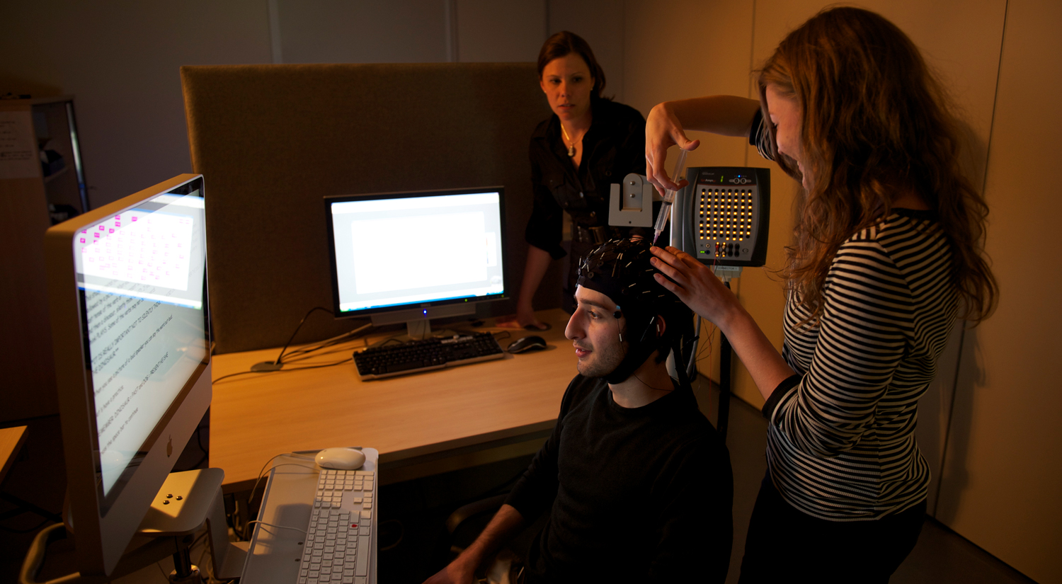 A student wearing an EEG cap is sitting in front of a large computer monitor. A second student is standing next to them, injecting some gel in to one of the cap sensors. Professor Silke Paulmann from the Department of Psychology is standing in the background, next to a second computer, watching them.