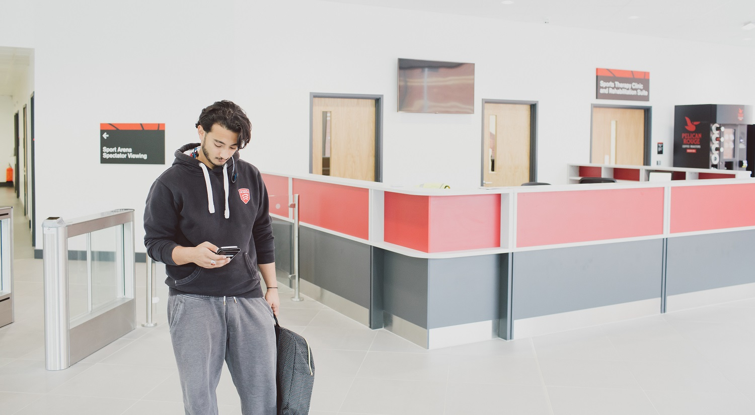 A student looking down at their phone in their right hand as they walk through the lobby of the Essex Sport Arena.