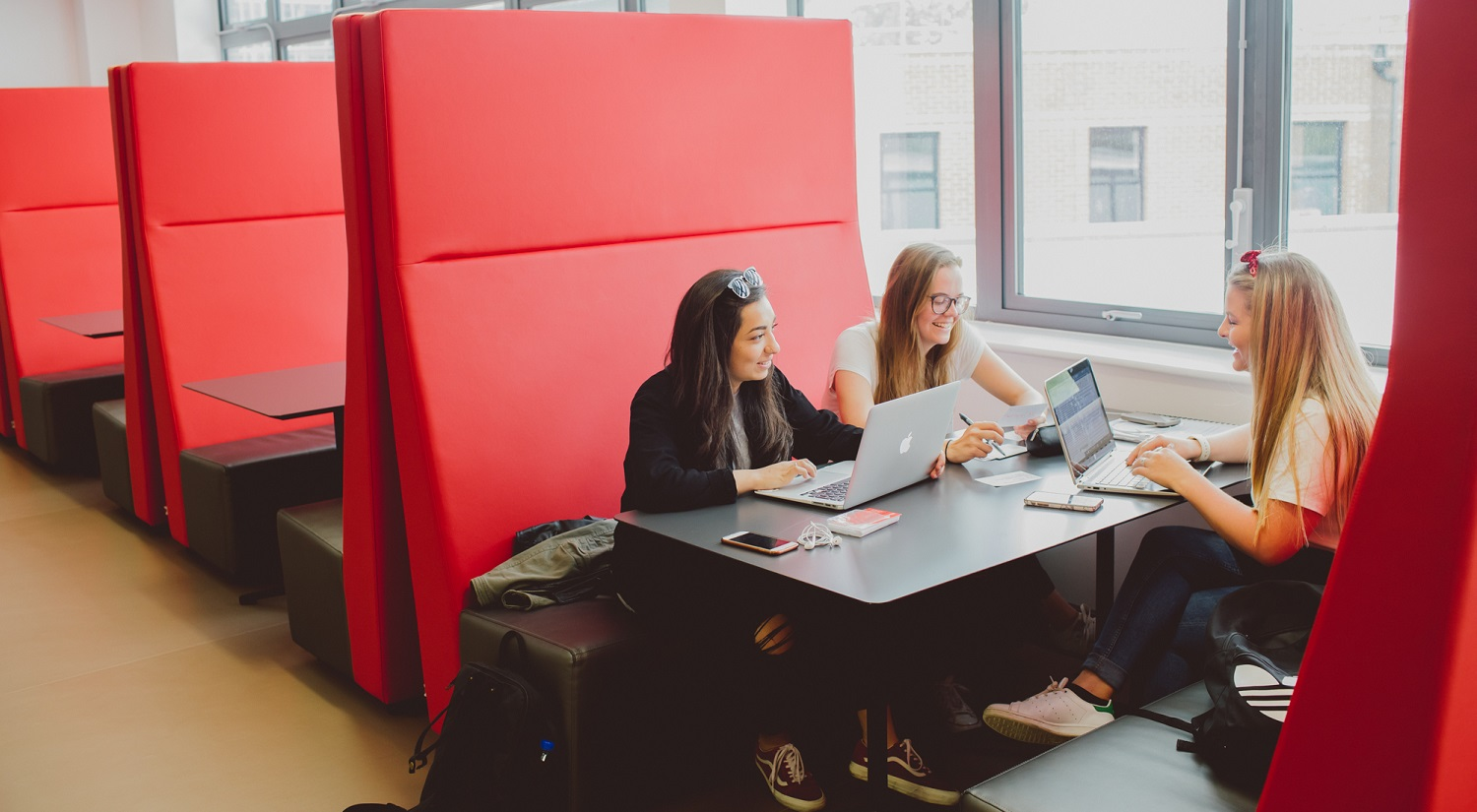 Three students sitting around a table with laptops and bags.