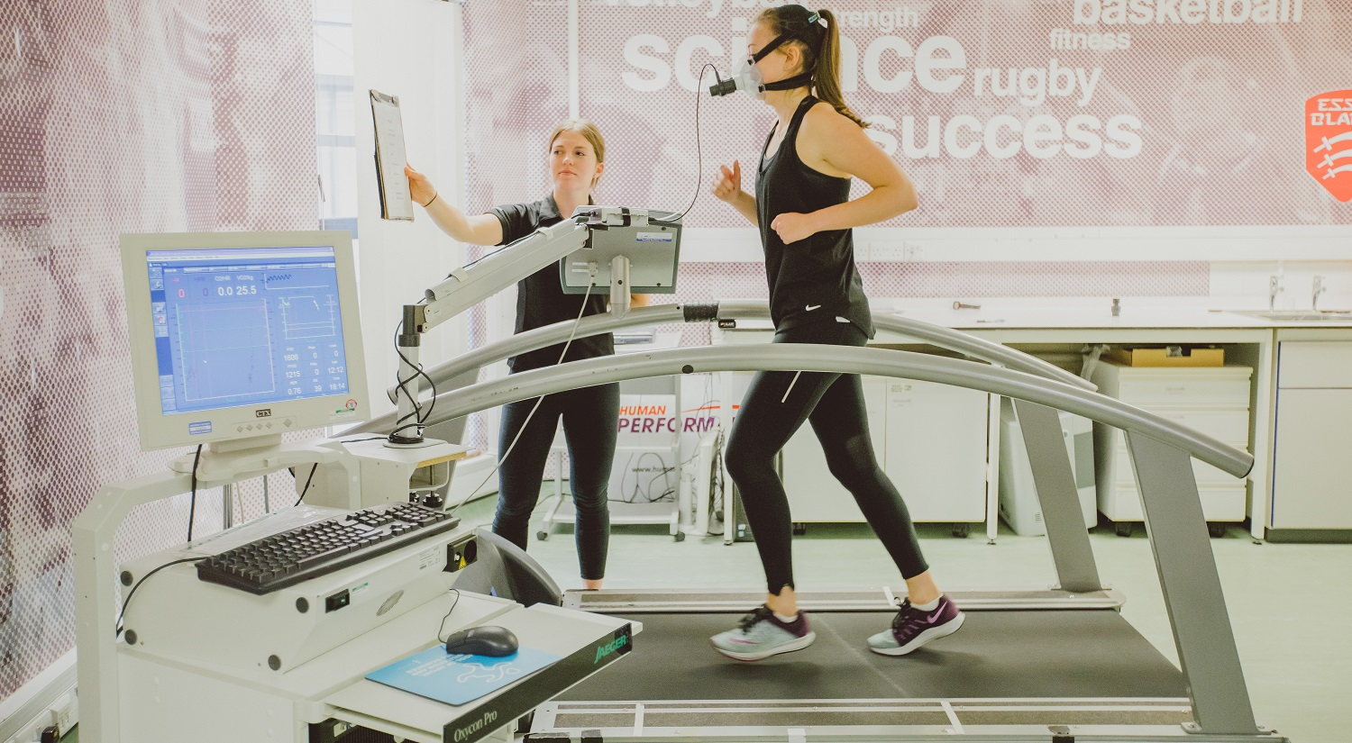 An athlete running on a treadmill while wearing a mask that may be measuring their breathing. A sports scientist is standing next to the treadmill, holding up a clipboard in front of the athlete. A computer tracking information from the athlete is in the foreground.