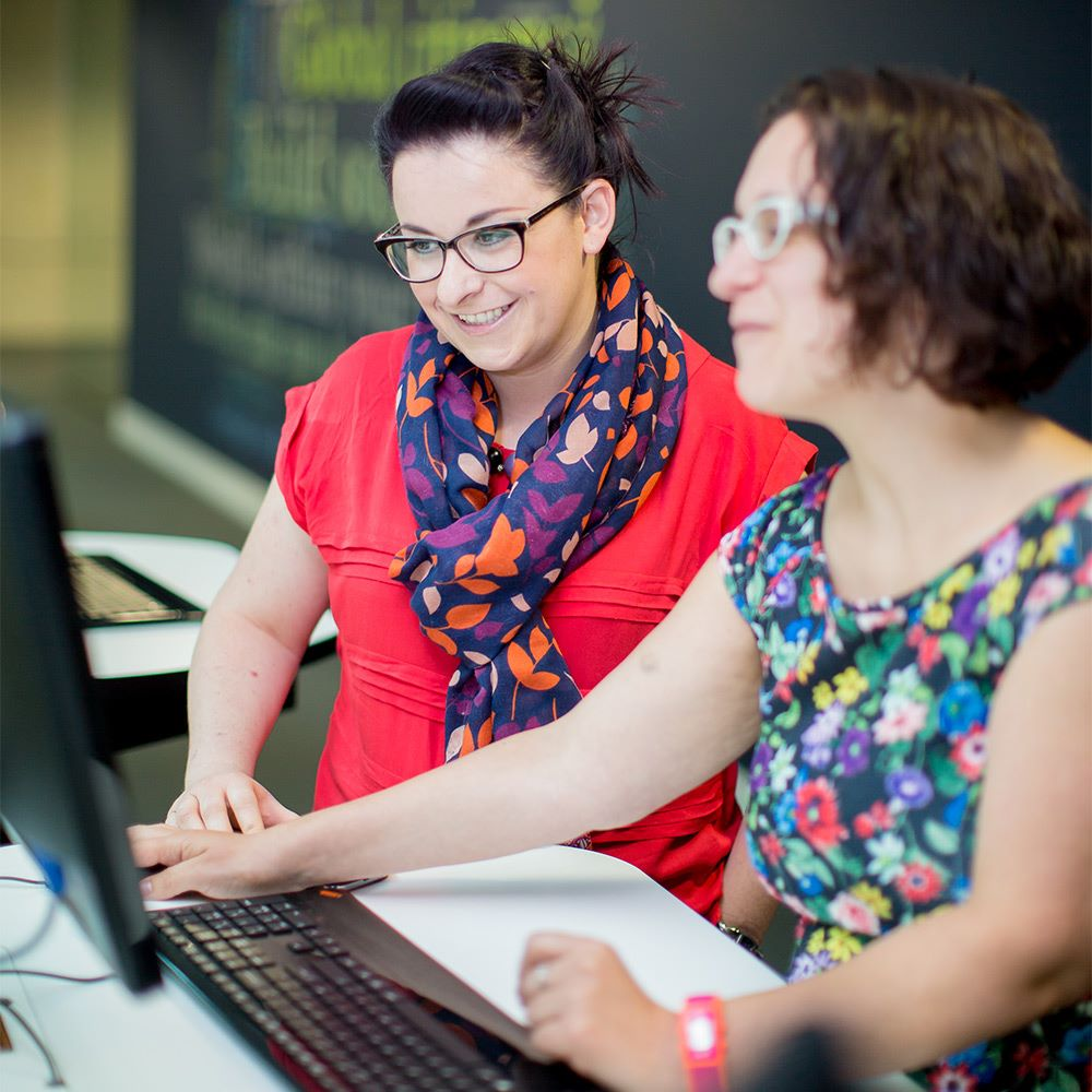 Two women looking at a PC screen