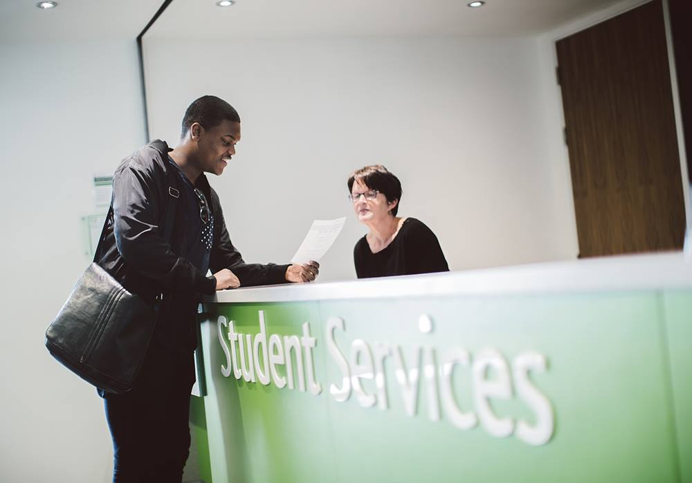 Student enquiring at student services desk