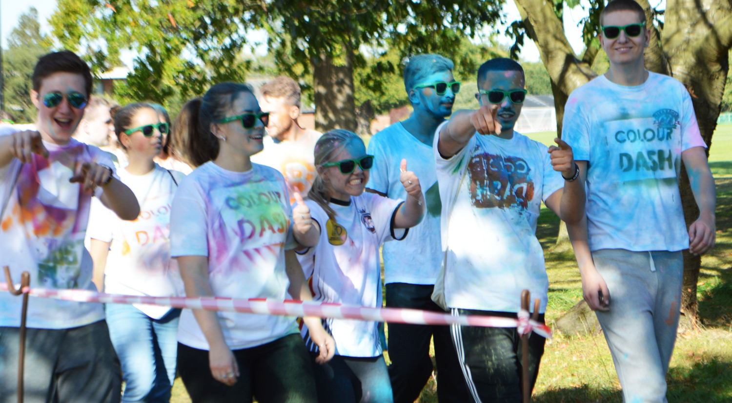 Group of students covered in coloured paints