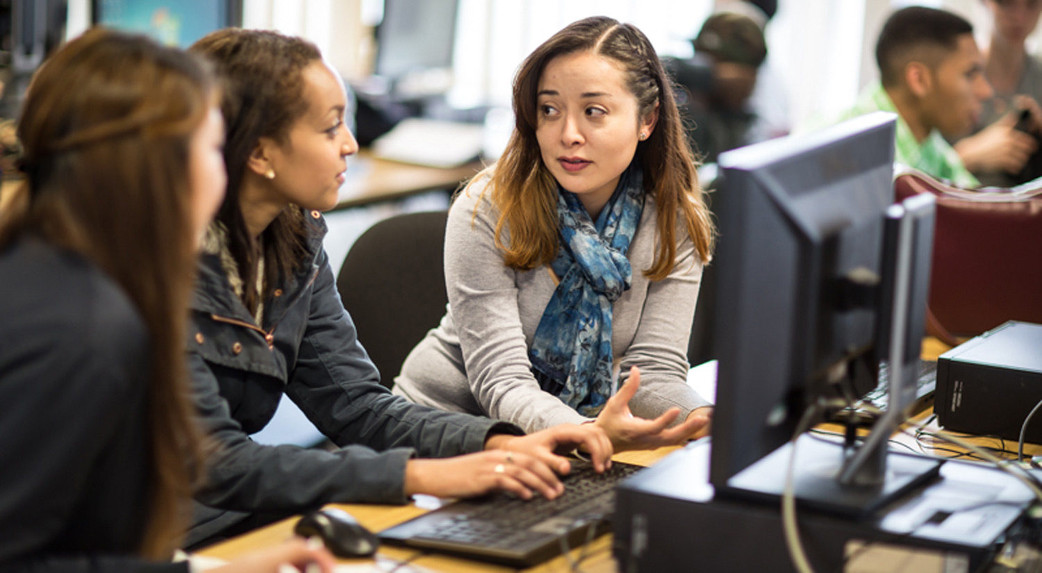 Image of three female students discussing work in a PC lab