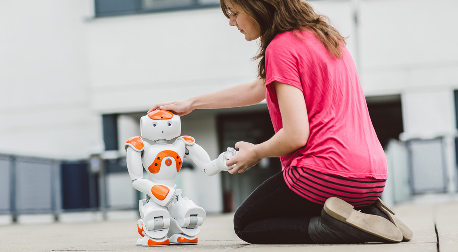 Image of a female student testing a Nao robot outside the computer science building