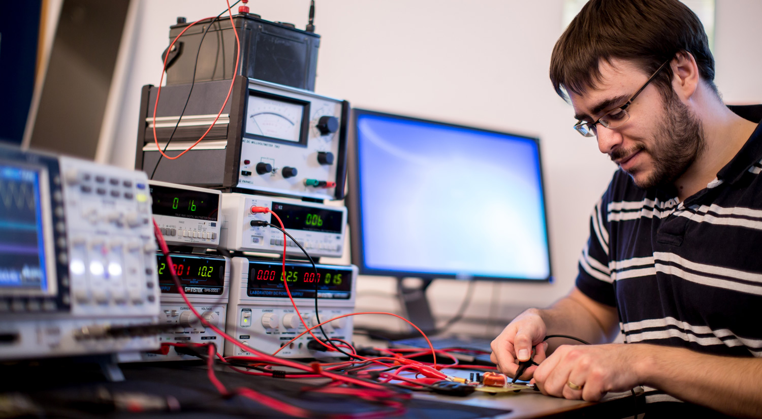 A student in an electronic labs working with equipment