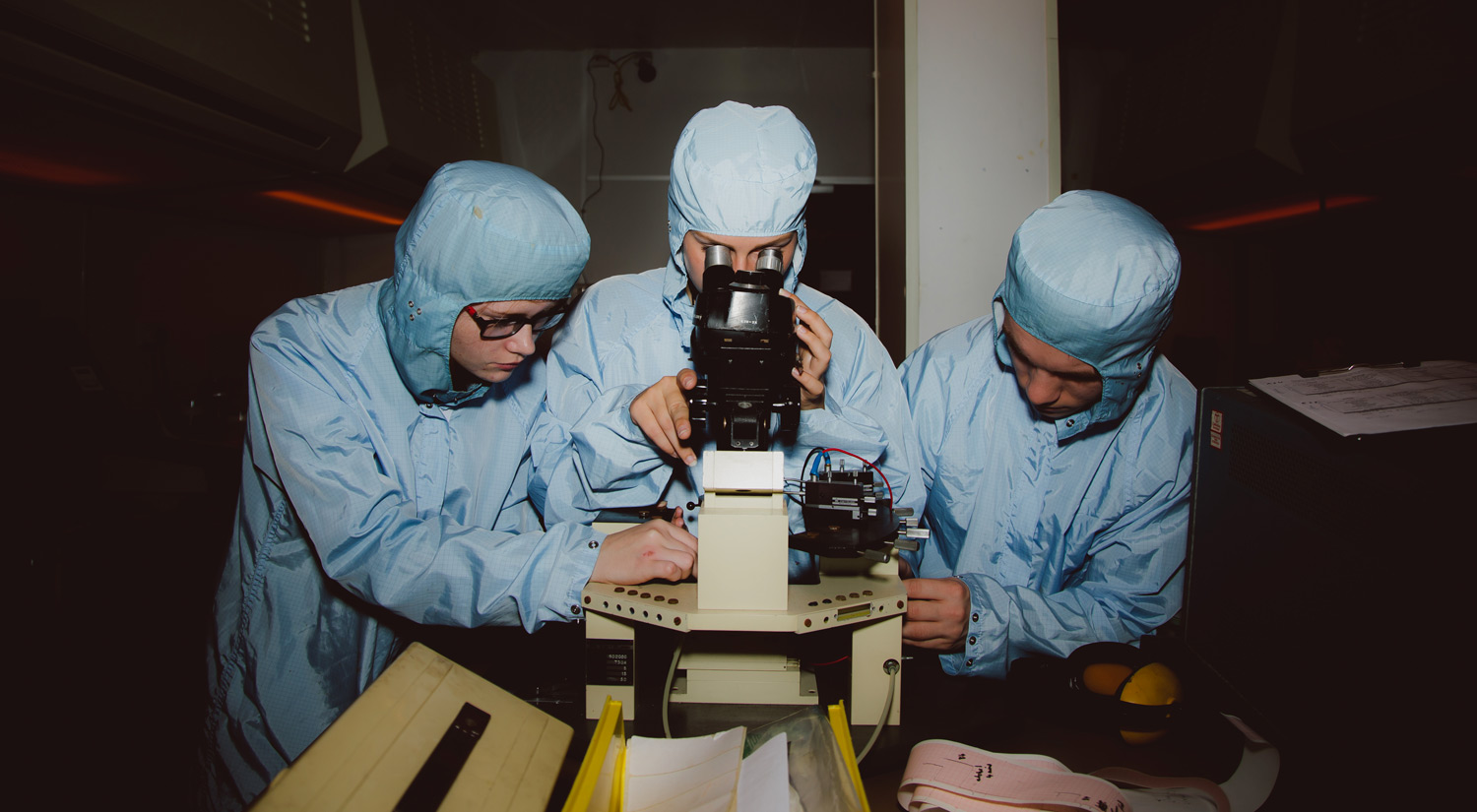 Three electronics students with lab coats using a microscope