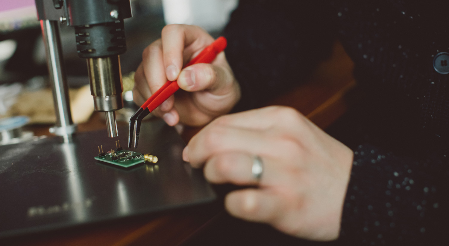 A close-up photo of a student working on a microchip under a microscope