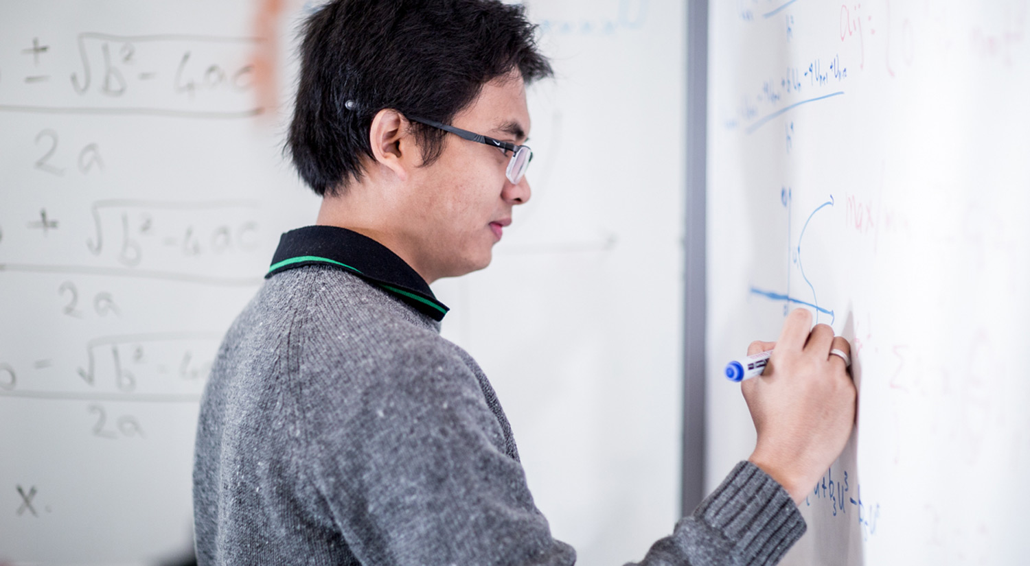 Image of a student working on a white board wall