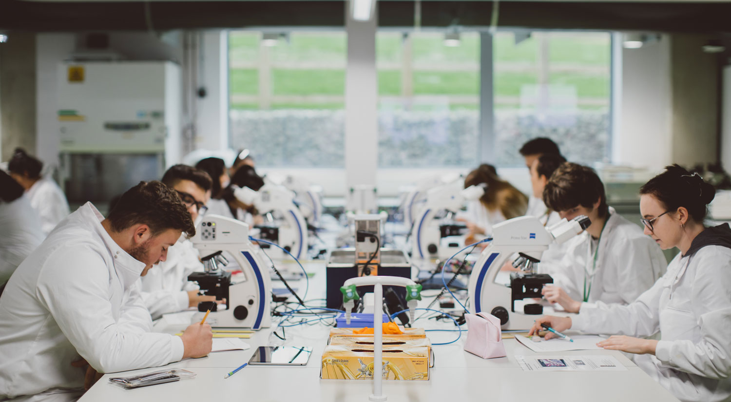 Students sitting in a lab wearing white coats looking into microscopes